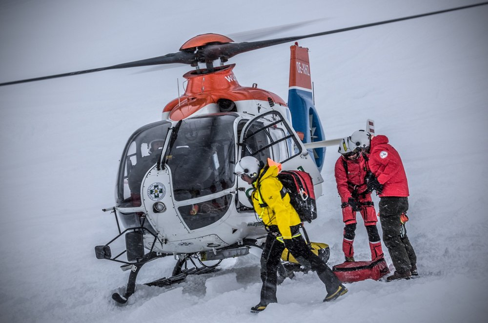 An Airbus H135 helicopter after landing in snowy conditions, with the pilot and crew on the ground