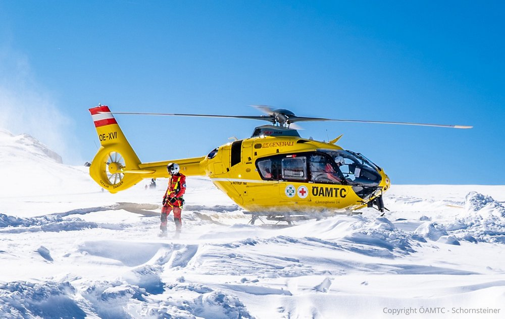 An Airbus-produced H135 helicopter flown by HEMS operator ÖAMTC is shown after landing on snow-covered terrain.