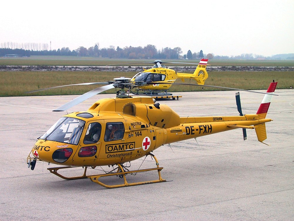 An Airbus-produced AS355 helicopter in the livery of ÖAMTC Air Rescue is shown in the foreground, with one of the operator's H135s visible behind it.