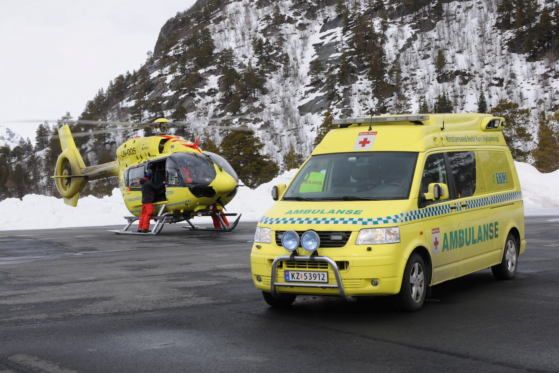 An Airbus helicopter on the ground with ambulance in the foreground.