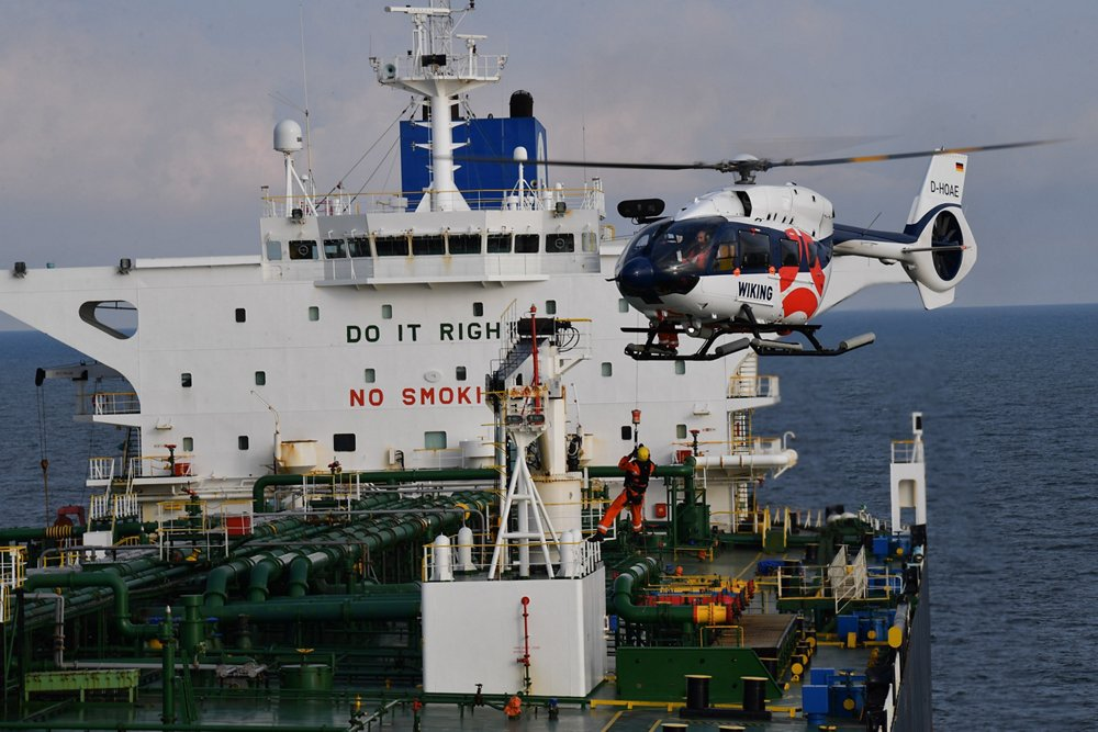 An Airbus H145 helicopter descends for landing on a ship.