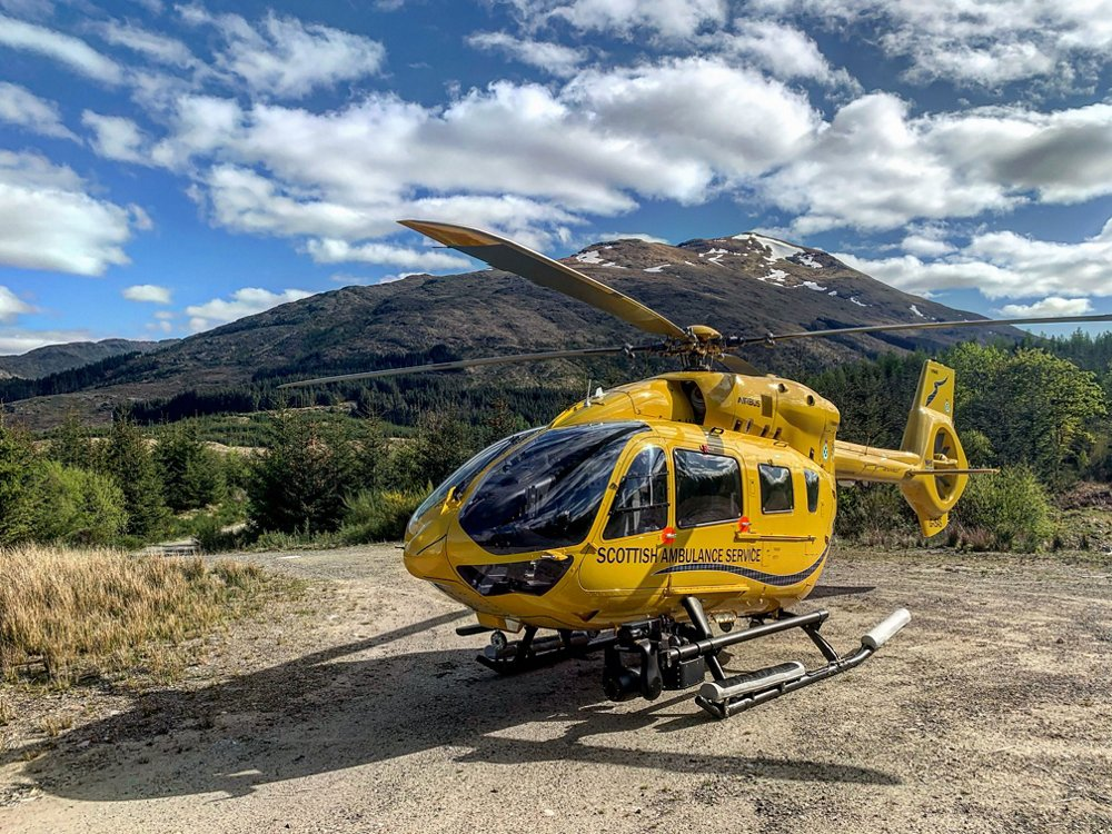 A parked H145 in the livery of Scottish Ambulance Service, with mountainous terrain in the background.