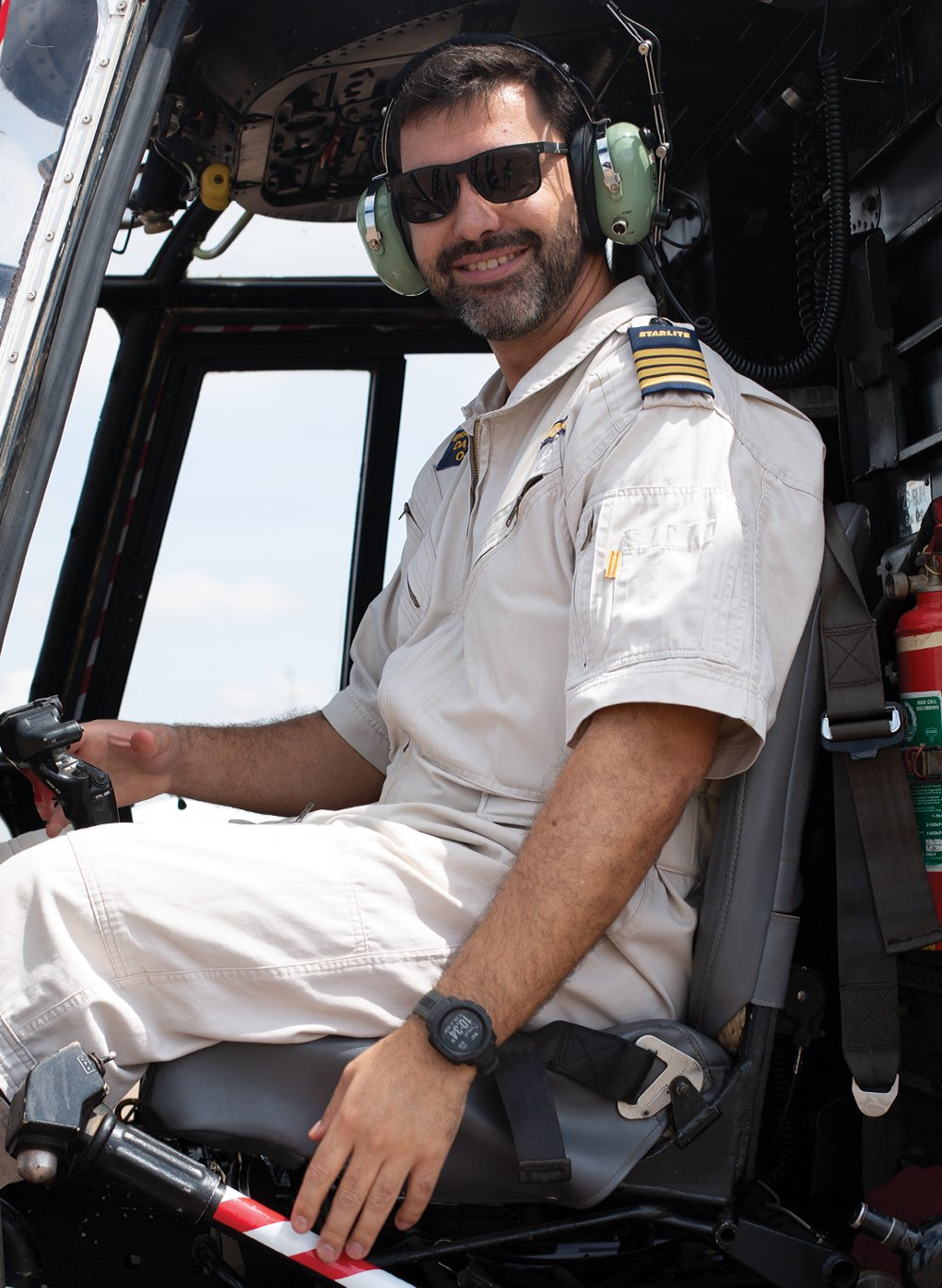 Starlite MEDEVAC pilot Captain Daniel Erasmus is shown behind the controls of a helicopter.