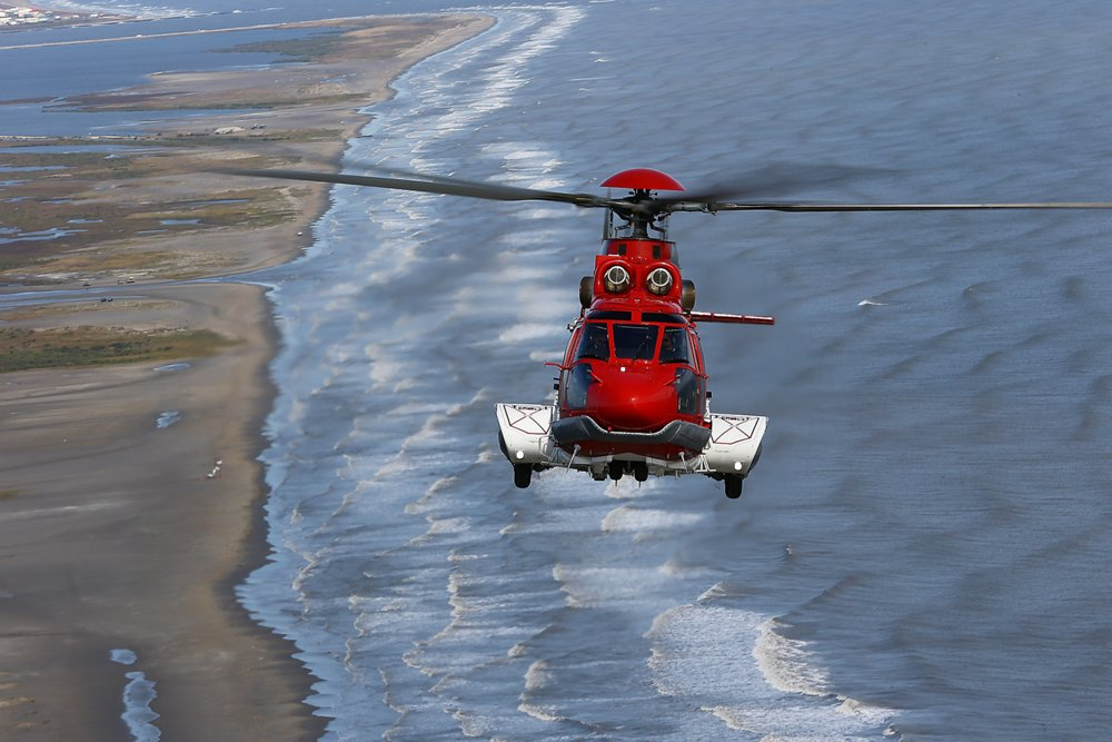 A head-on view of an Airbus-produced EC225 helicopter flying over a coastal setting.