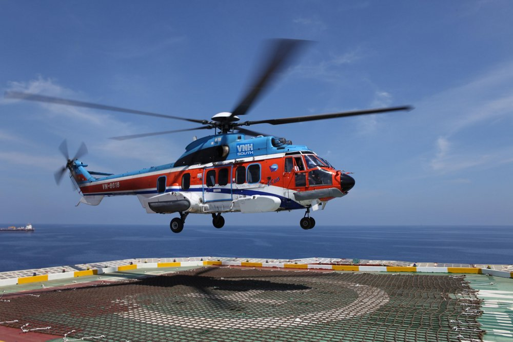 An Airbus H225 helicopter delivered to VNH South hovers over a helipad.