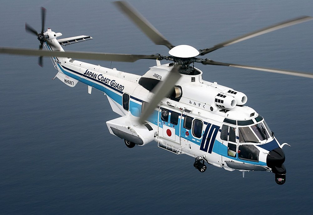 Side view of an in-flight Super Puma helicopter operated by the Japan Coast Guard.