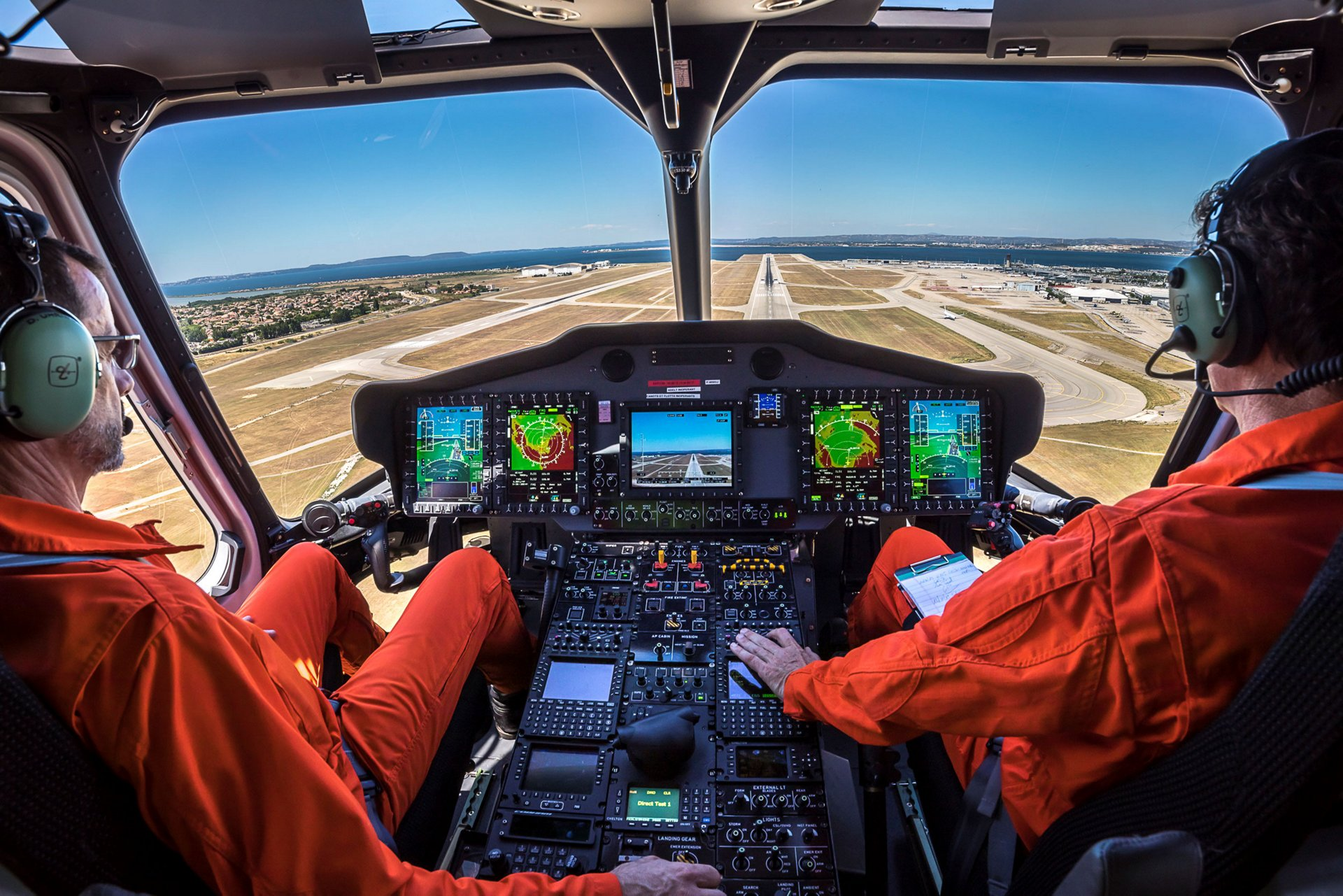 A view of two pilots behind the controls of a rotorcraft incorporating Airbus' Helionix avionics suite.