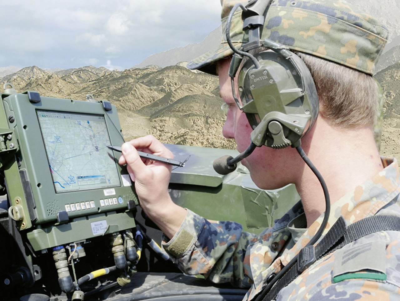 A member of the military uses a tablet device and stylus for mission planning.