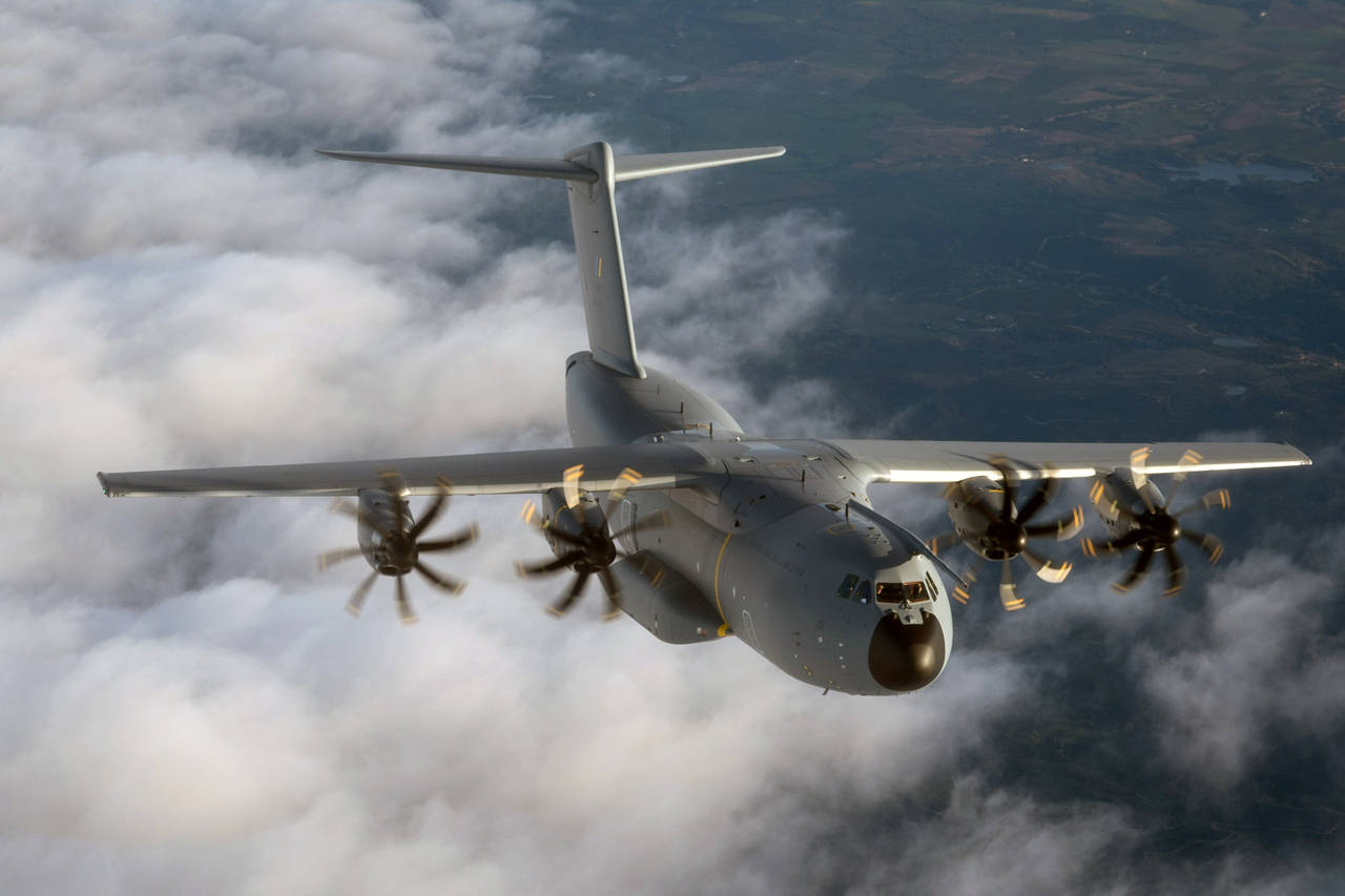 A view of an A400M military airlifter flying above clouds.