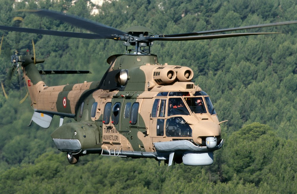 A Mark I Cougar helicopter is shown flying over a wooded area.