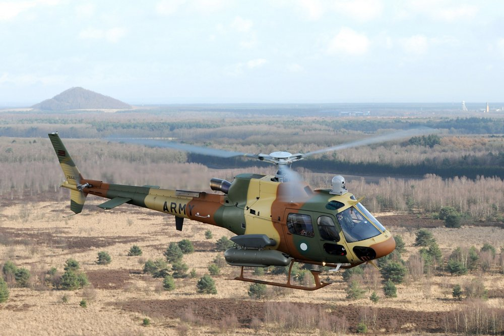 An in-flight Airbus H125M military helicopter with camouflage colouring.