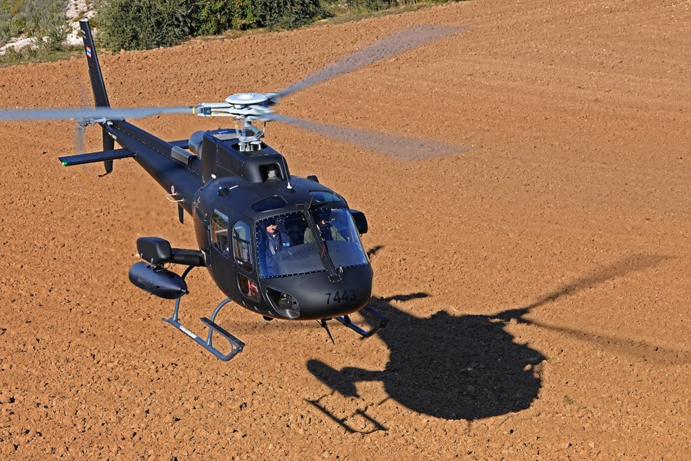 An Airbus H125M military helicopter configured for ISTAR (intelligence, surveillance, target acquisition, and reconnaissance) and attack missions hovers over the ground.