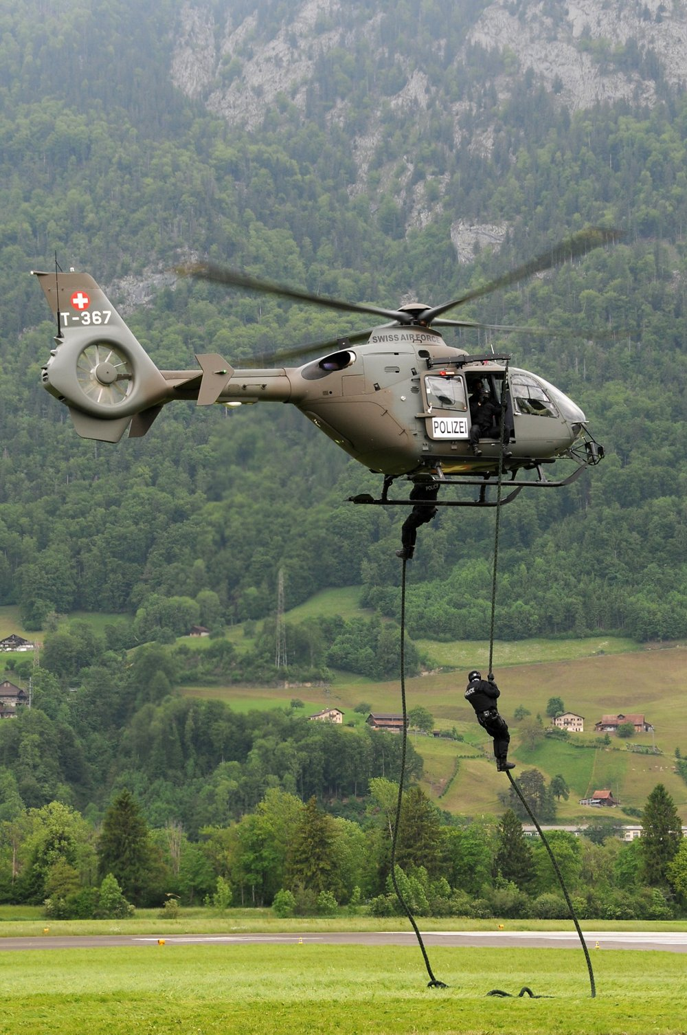 Police officers rappel from a Swiss Air Force H145 law enforcement helicopter.
