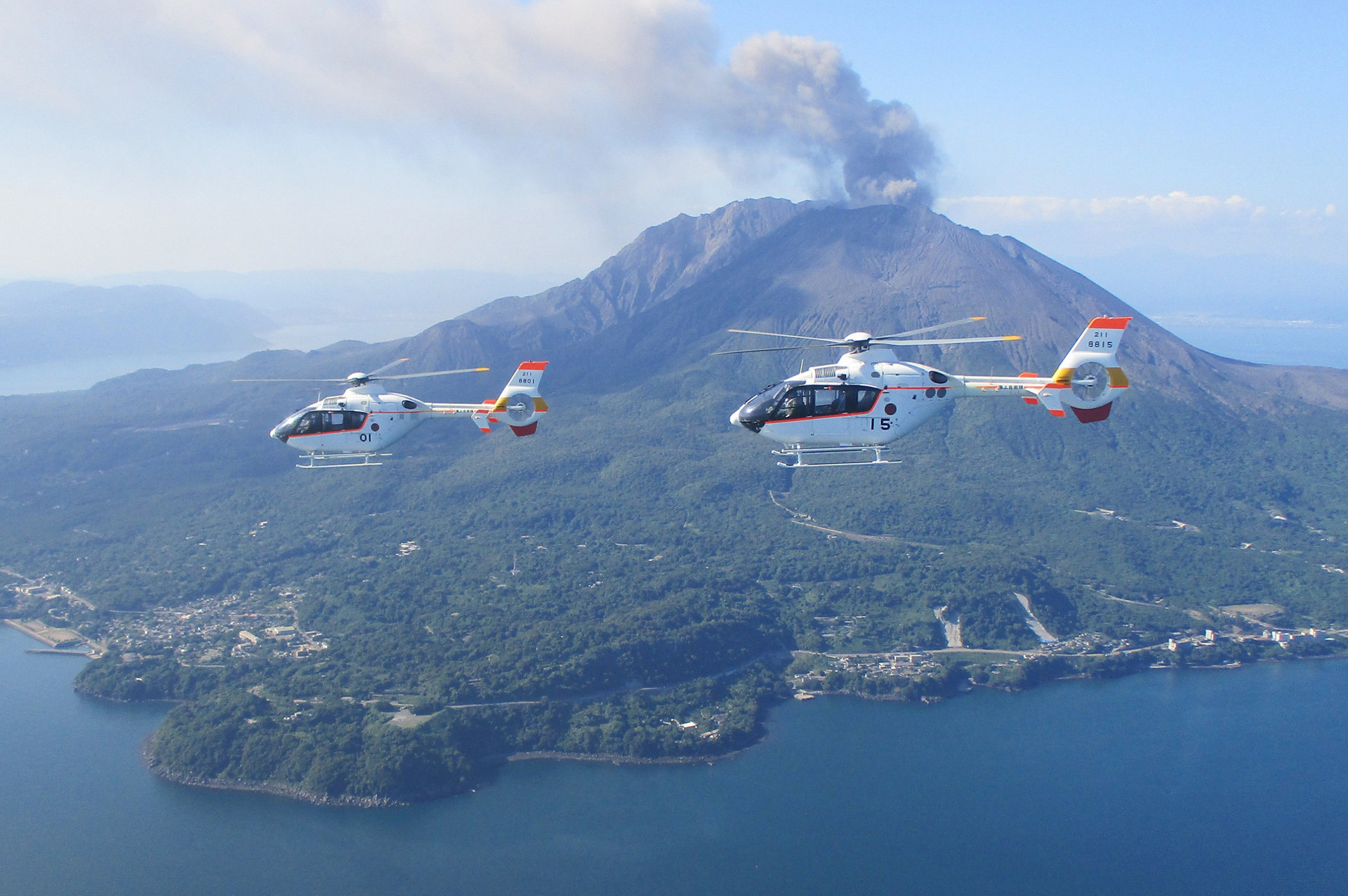 Two H135s operated by the Japan Maritime Self-Defense Force (JMSDF) fly near a volcano.