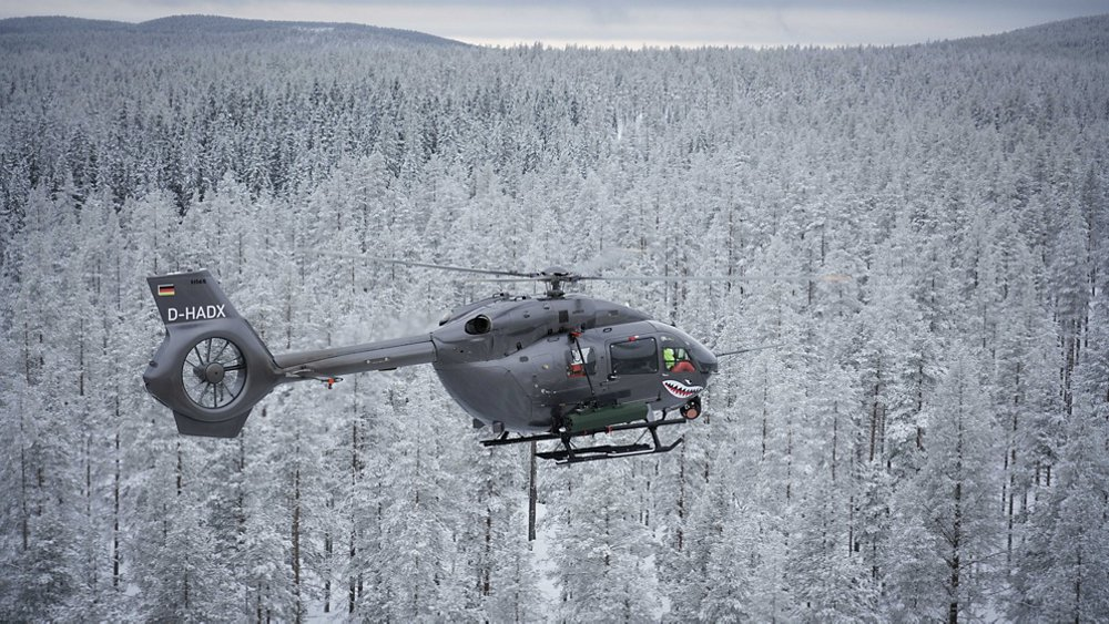An Airbus H145 helicopter flies over snow-covered, wooded terrain.