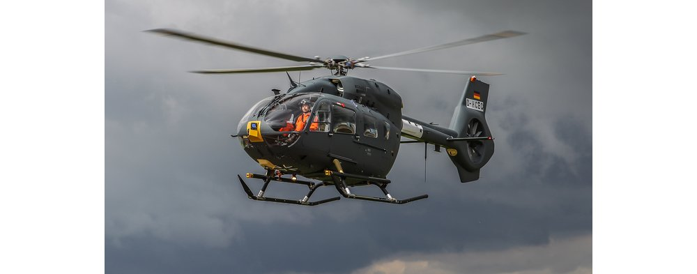 An in-flight Airbus H145M helicopter with a clear view of the pilot inside.