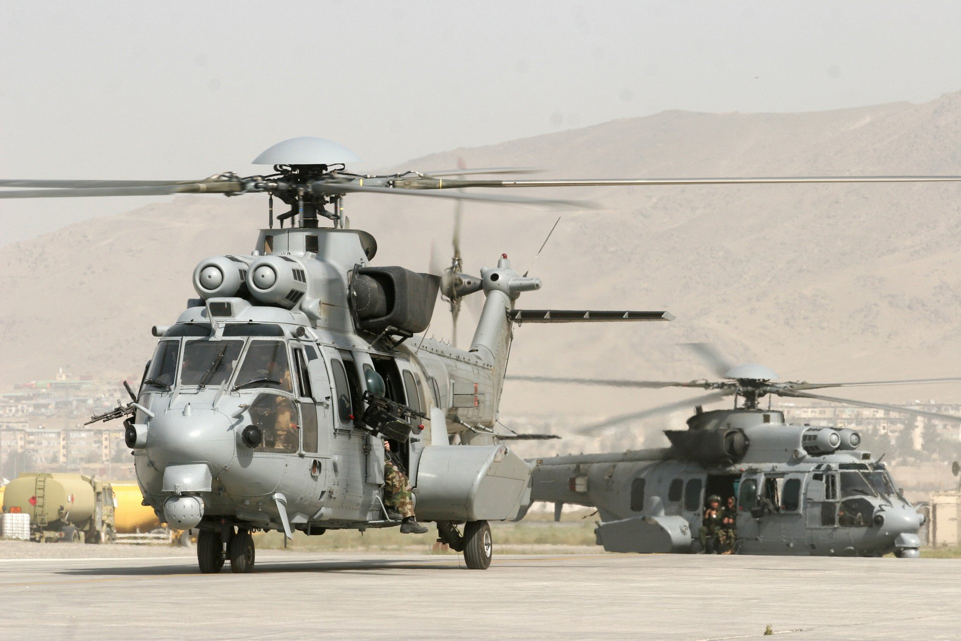 A pair of Airbus H225M military helicopters on the ground with their main and tail rotor systems turning.