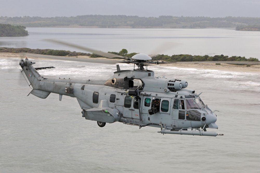 An H225M military helicopter flies over a coastal setting.