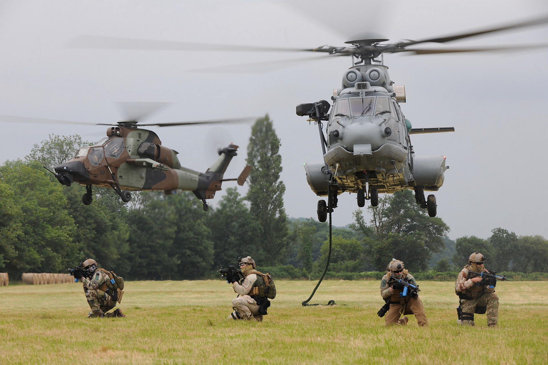 An H225M is shown during ascent with a Tiger HAD helicopter in the background.