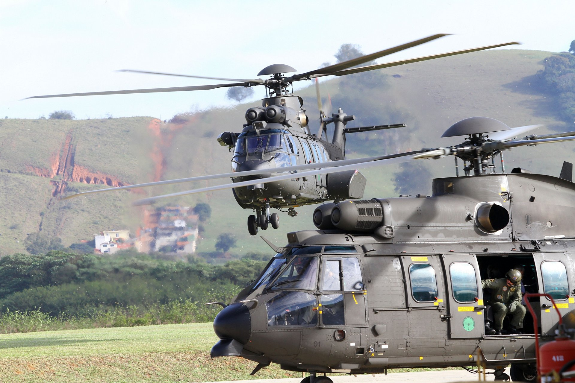An H225M is shown in flight, with another on the ground.