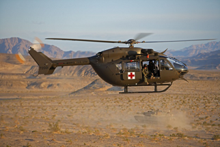 A U.S. Army UH-72A Lakota  from the USAAAD (Fort Irwin, California) cruises over the desert past a M1A2 Abrams main battle tank
