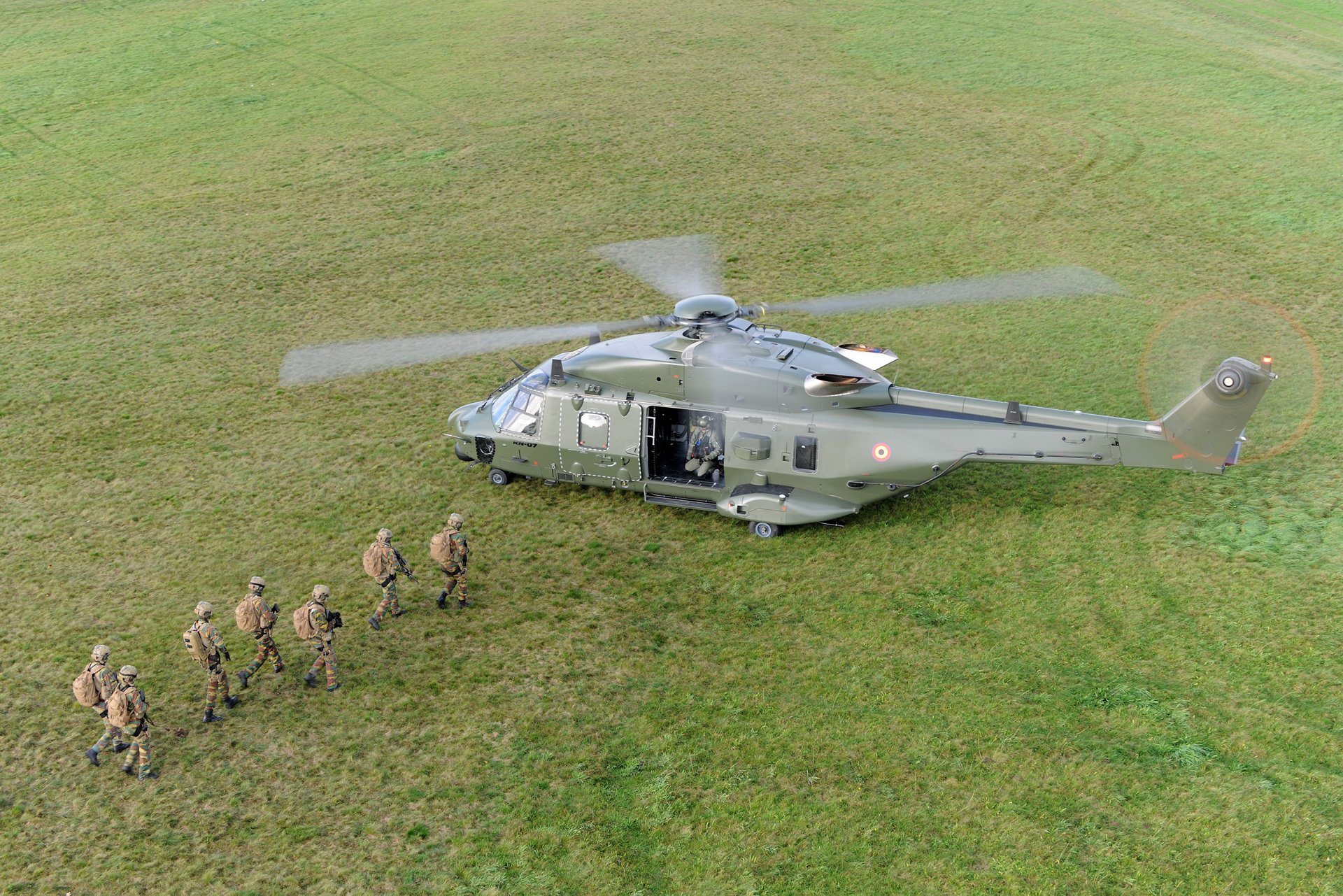 A group of seven military troops advance toward an on-ground NH90 helicopter.