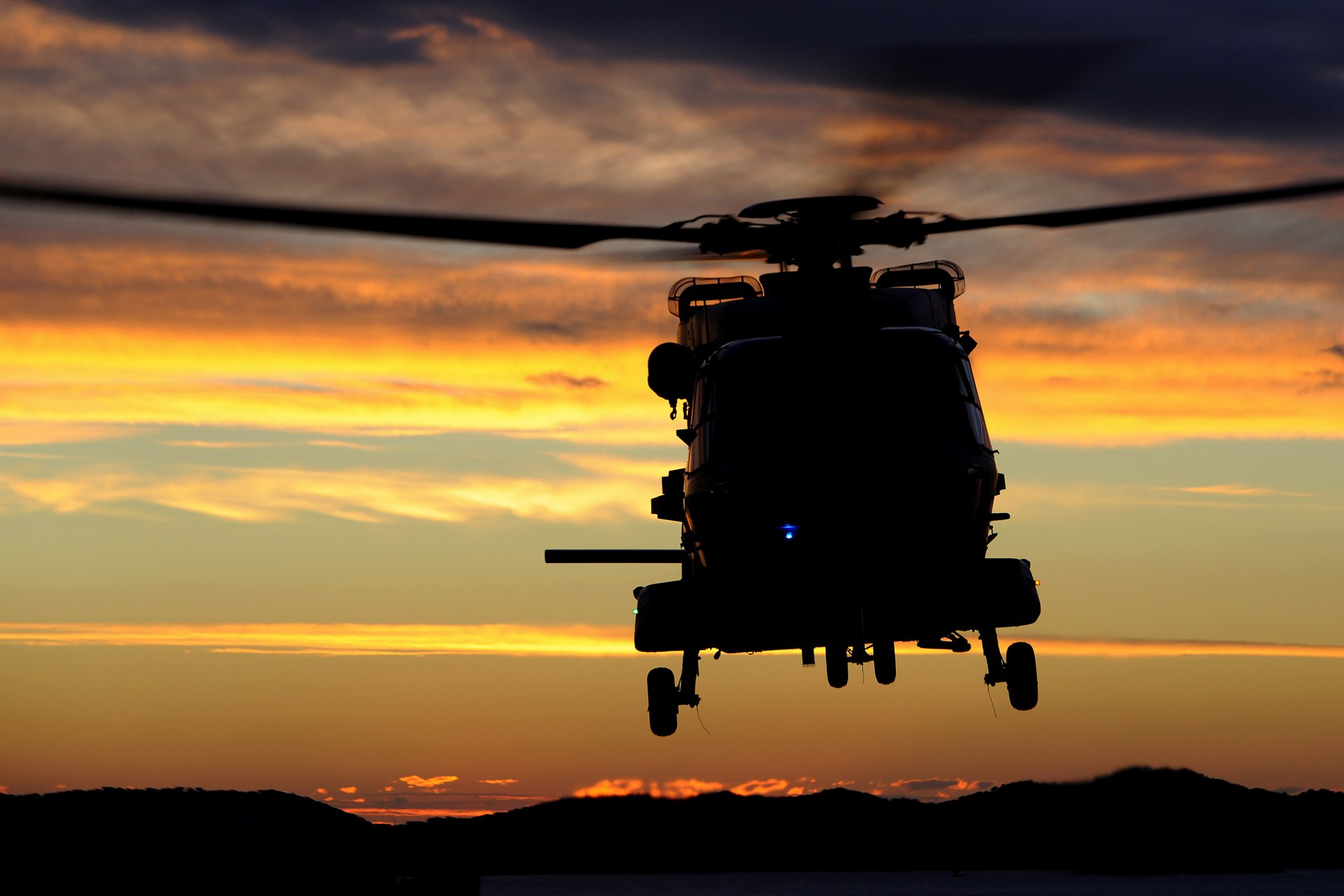 Front view of a NH90 NFH flying over the sea at the susnset