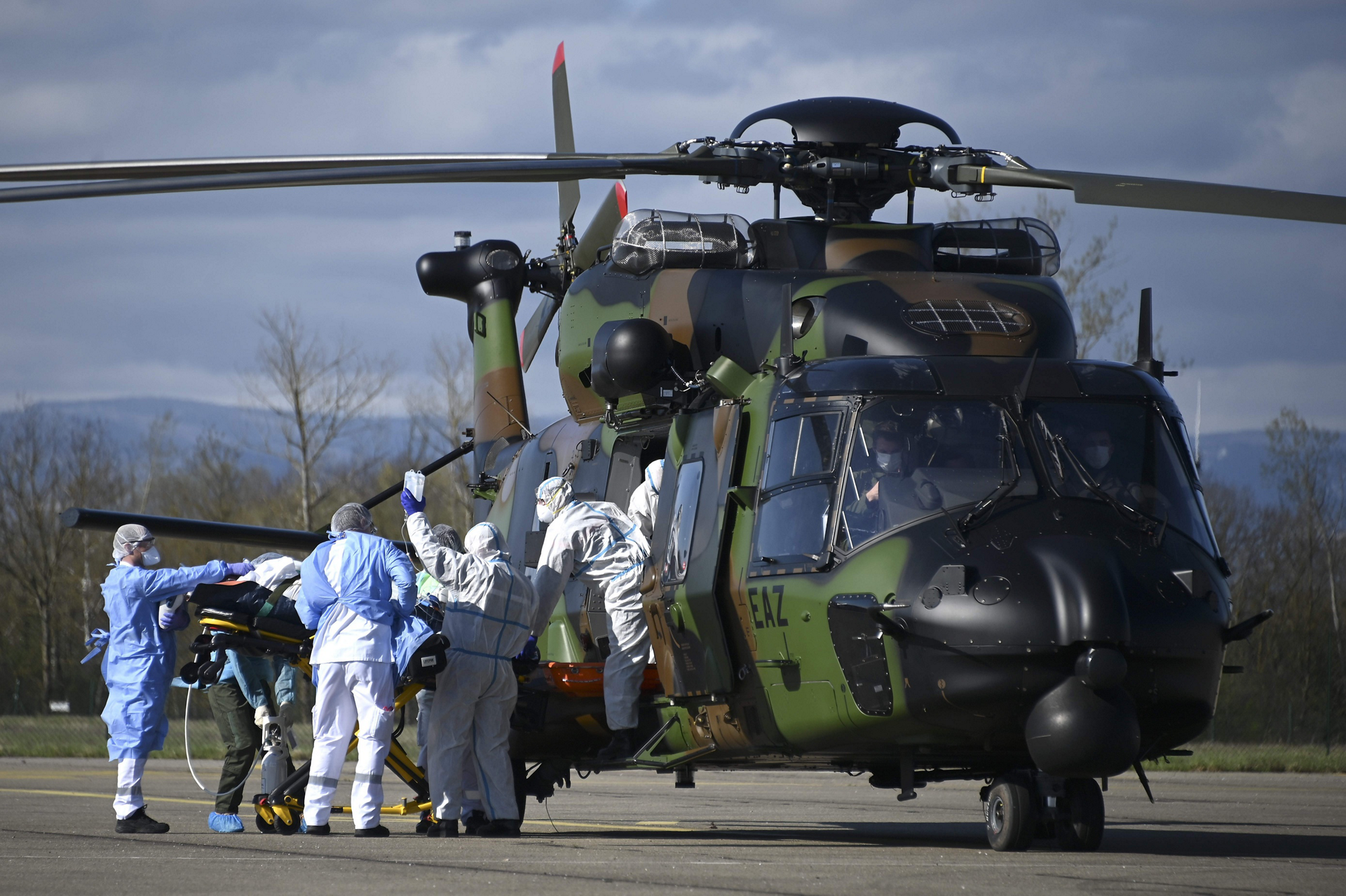 Medical staff push a Covid-19 patient on a stretcher towards the 1st Combat Helicopter Regiment's (RHC) NH90 in Strasbourg, on March 30, 2020.