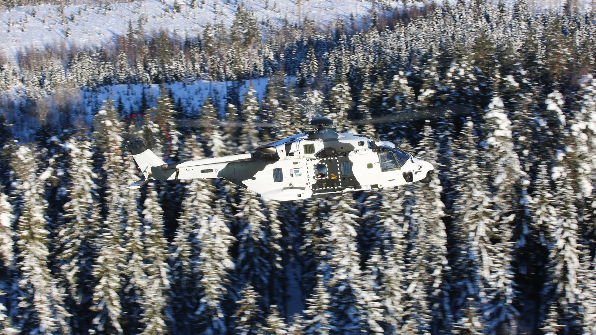A Finnish Army NH90 is shown in flight with a camouflage paint scheme.