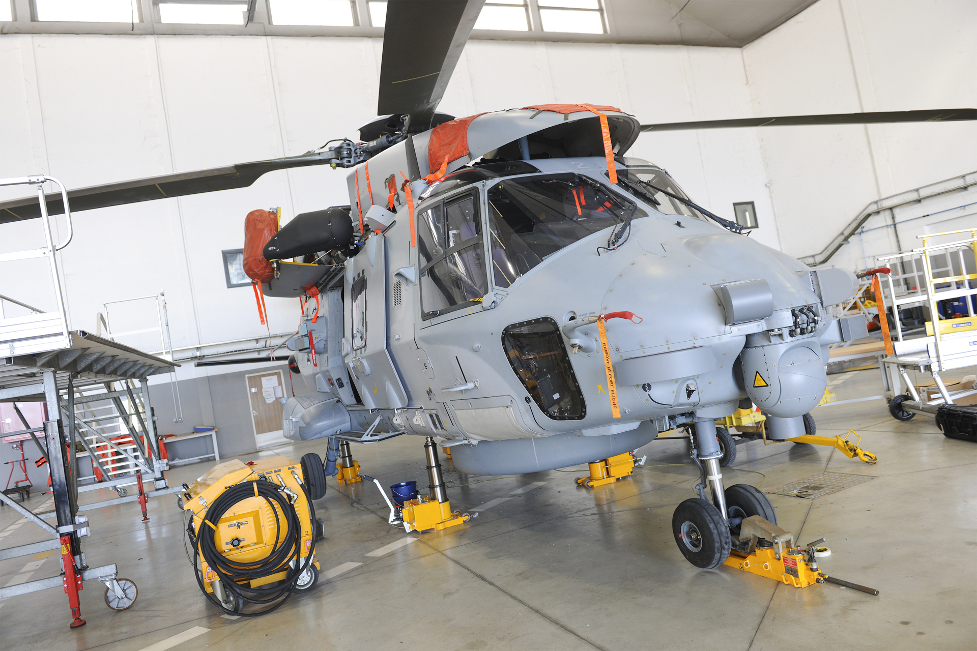 An NH90 helicopter is shown inside a maintenance facility, ready for servicing.