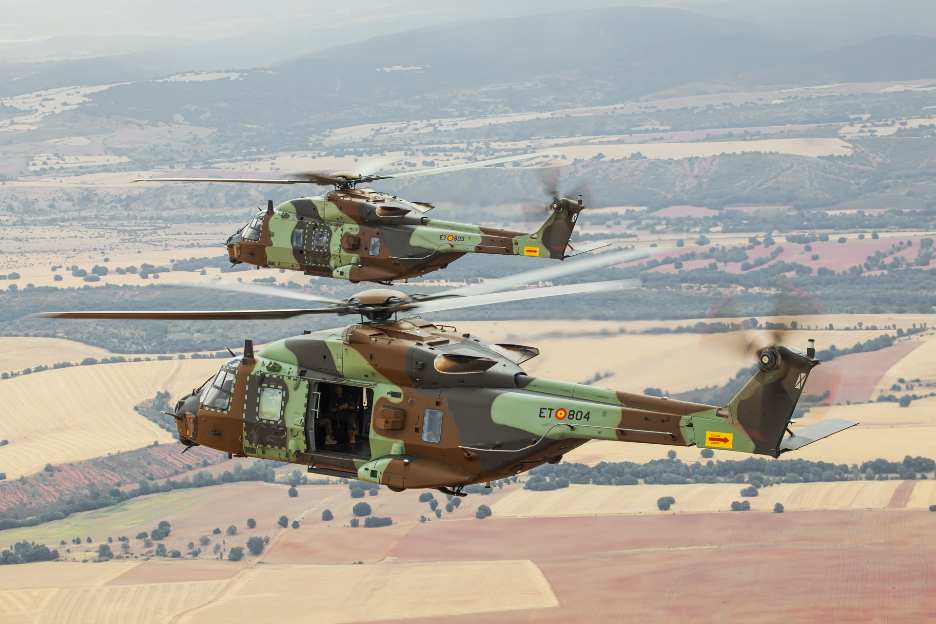 Two Spanish NH90s in the Standard 2 configuration are shown in flight.