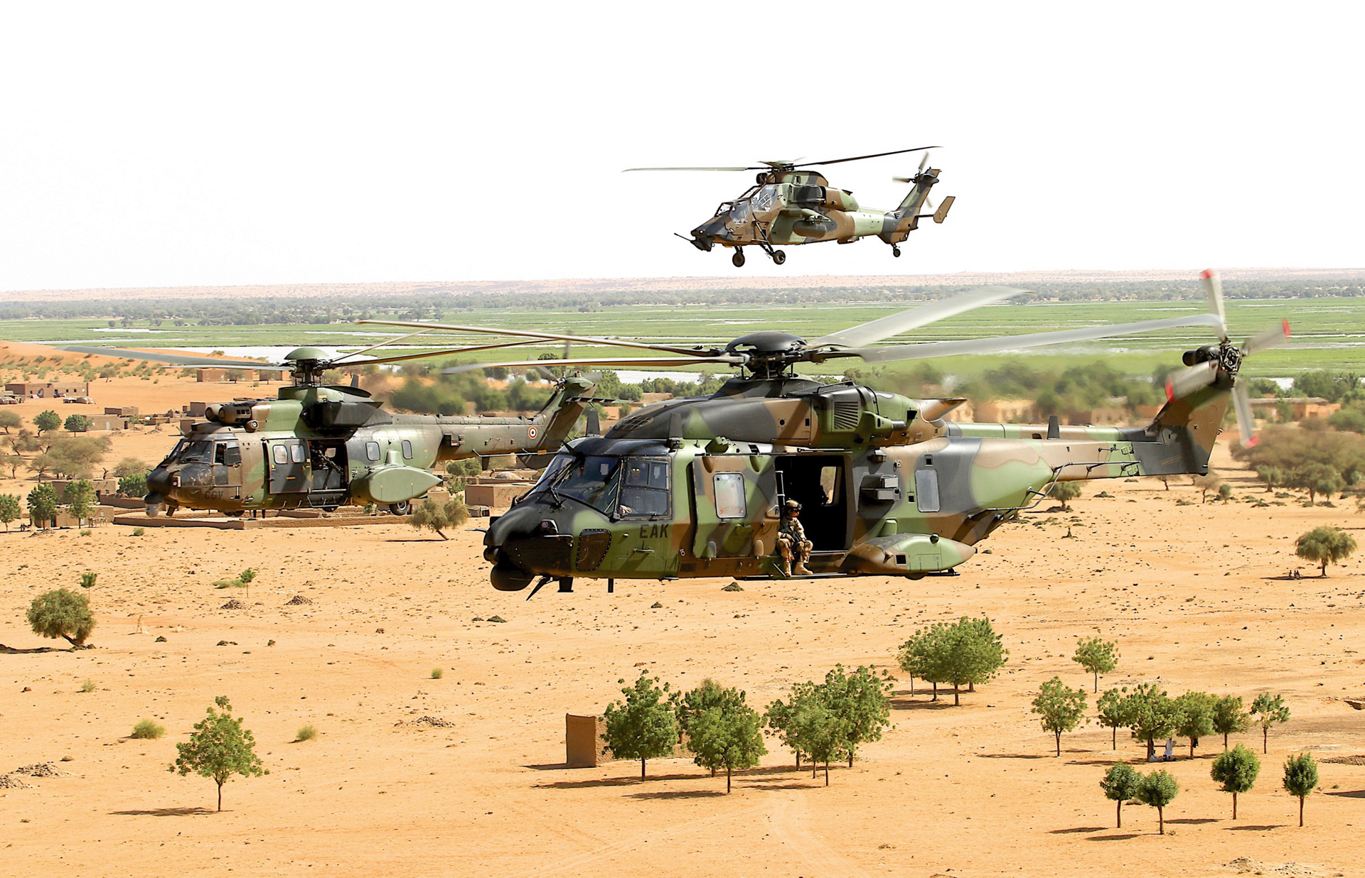 An NH90 and a Tiger helicopter fly in formation.
