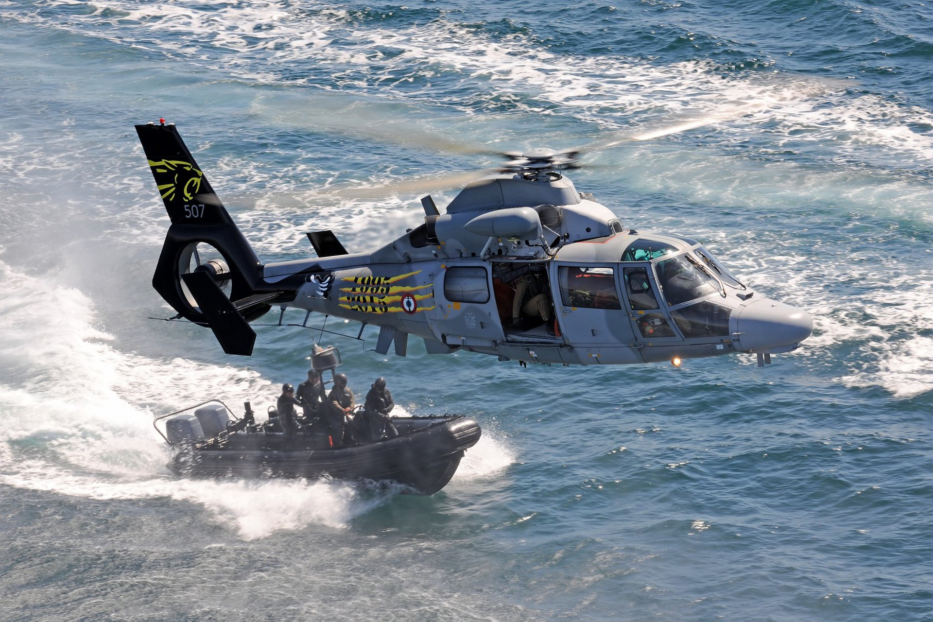 An Airbus AS565 MBe military helicopter of the French Navy flies over a vessel with commandos.
