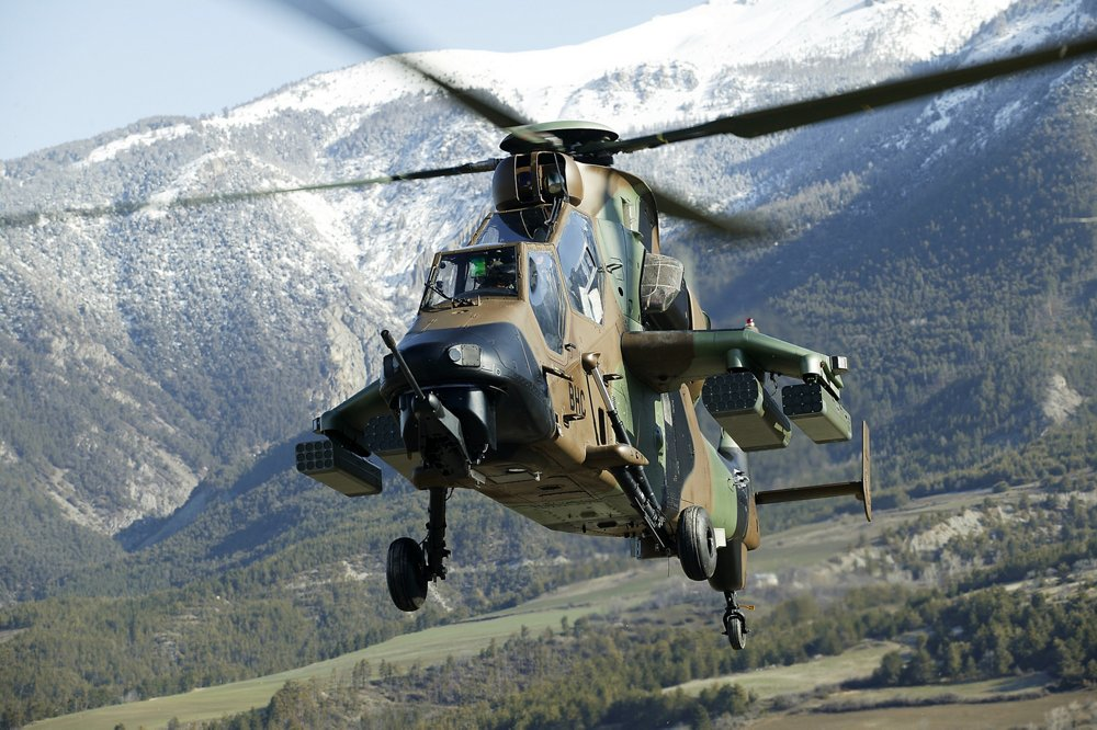 An Airbus-produced Tiger combat helicopter flies in a mountainous area.
