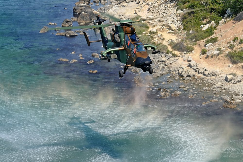 An Airbus Tiger HAD multi-role attack helicopter hovers over coastal terrain.