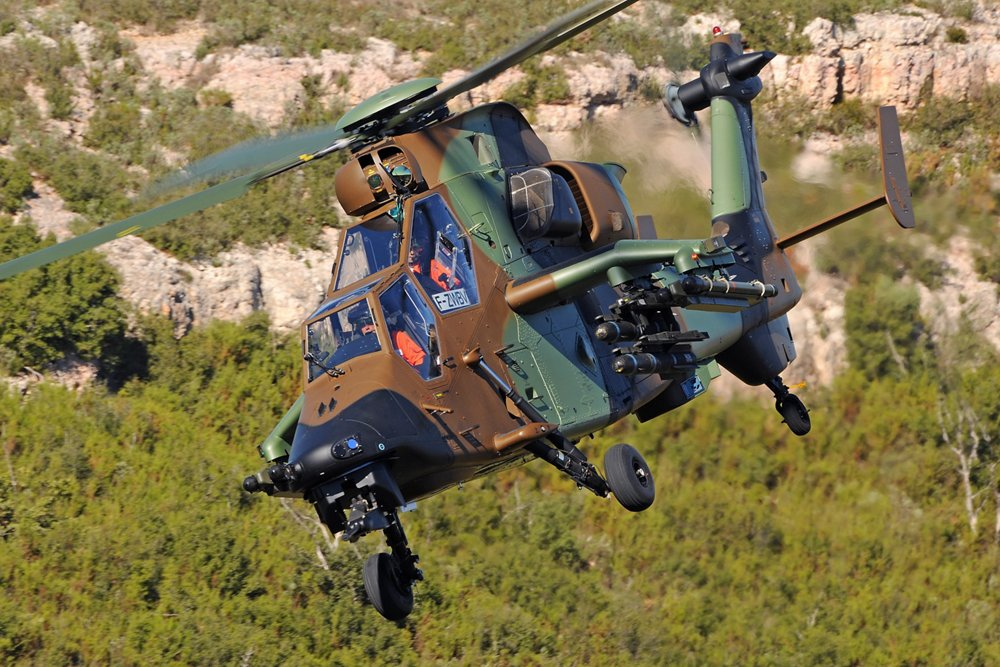 An in-flight Airbus Tiger HAD military helicopter with side-mounted weapon systems.