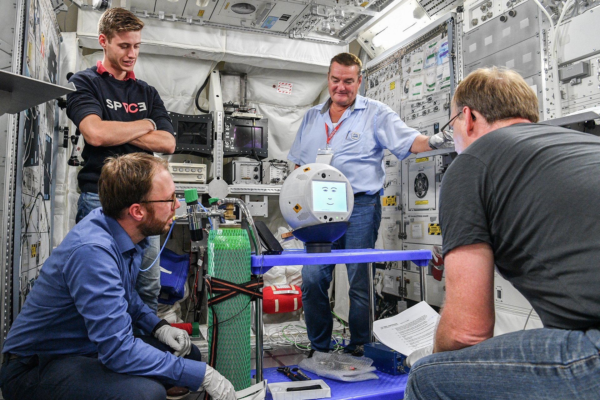 CIMON-2 under test:  (from left) Christian Karrasch (DLR), Julien Doche (Airbus), Reinhard Schönfelder (Airbus) and Bernd Rattenbacher (BIOTESC). 