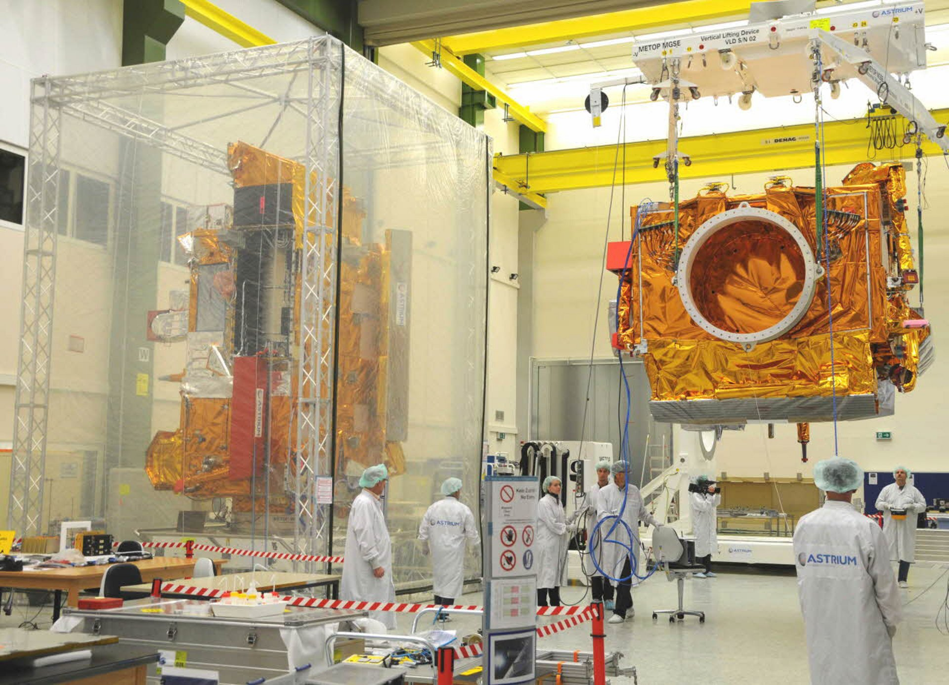 The Airbus-produced Metop-B meteorological satellite is transferred within a clean room facility.