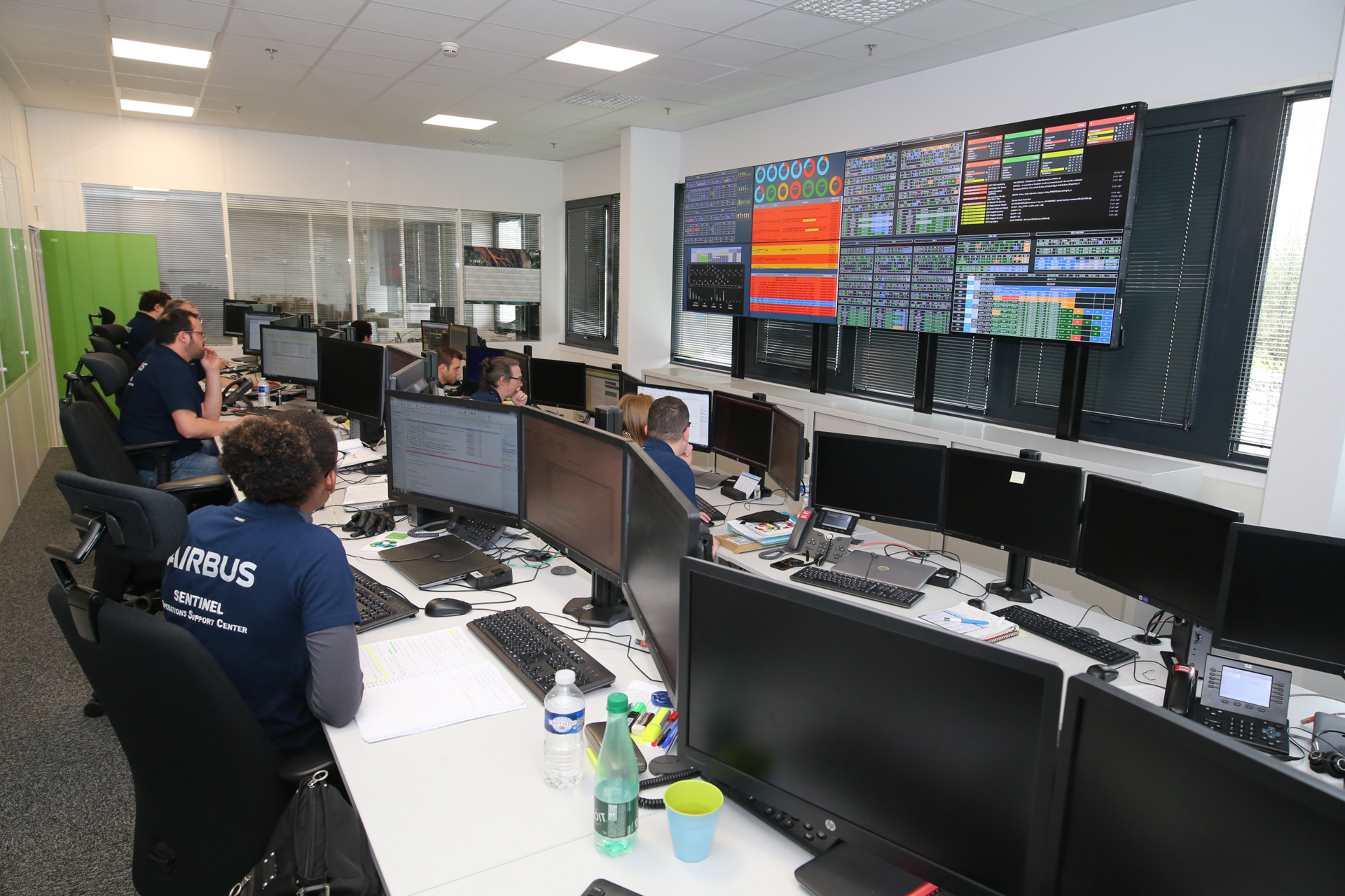 Airbus Defence and Space team members review data on monitors.