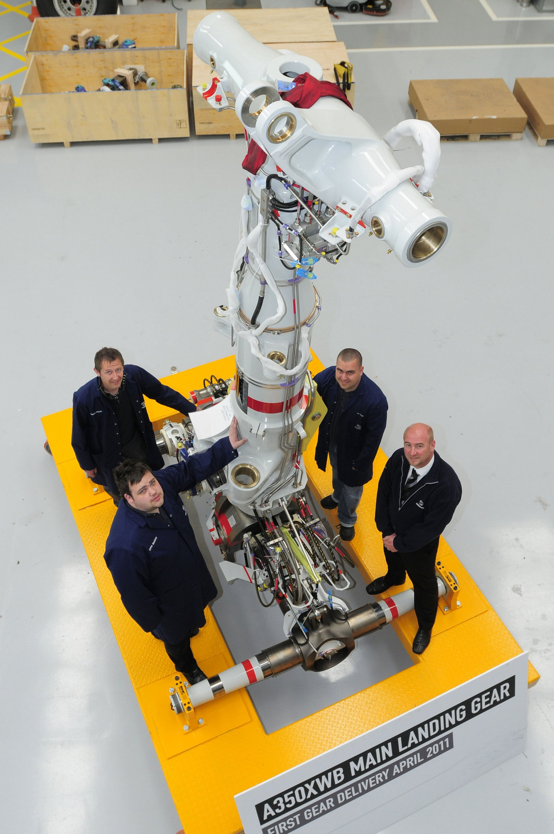 The A350 XWB landing gear in the Sir George White Building at Airbus, Filton, with from left, Robert Pimm, lead installation engineer, Chris Buckley, design engineer, Lee Poole, test engineer, and Steve Merrick, head of landing gear development and operations.