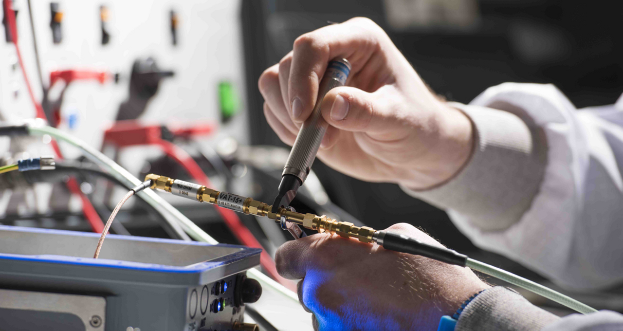 A DeckFinder component undergoes maintenance, with the focus on an engineer's hands and tools.