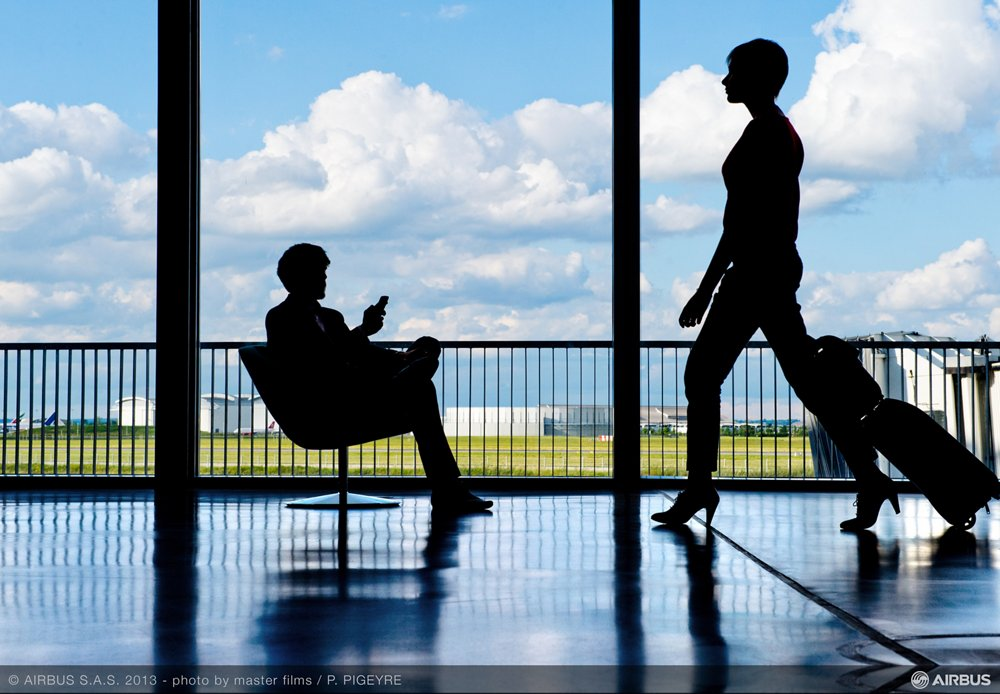The silhouettes of two travellers at an airport facility